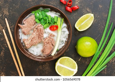 Traditional Vietnamese pho soup on a dark rustic background, lime, green onions, chili. View from above