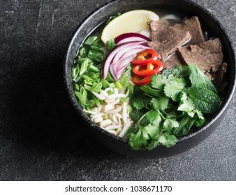 Traditional Vietnamese soup  Pho bo of beef, rice noodles and greens in a black bowl on a gray background. Asian food concept. Top view