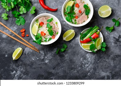 Traditional Vietnamese Soup Pho Bo with Rice Noodles, Beef and Herbs on Dark Background, Asian Cuisine