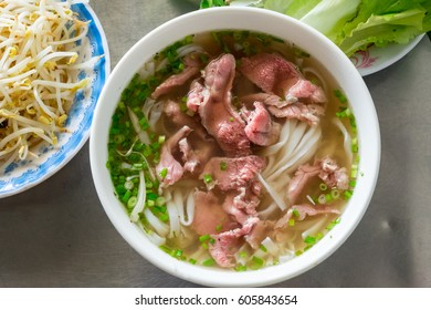 A traditional Vietnamese soup Pho Bo, with raw beef, green onions, soy sprouts