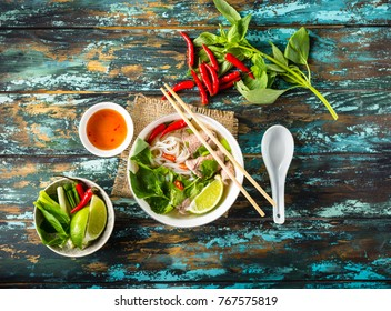 Traditional Vietnamese soup Pho bo with herbs, meat, rice noodles, broth. Pho bo in bowl with chopsticks, spoon. Top view. Asian soup Pho bo, wooden table background. Vietnamese authentic tasty soup