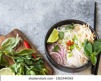 Traditional Vietnamese soup- pho ga in black bowl with chicken and rice noodles, mint and cilantro, green and red onion, chili, bean sprouts and lime on grey background.  Asian food. Copy space