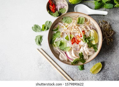 Traditional Vietnamese soup- pho ga in bowl with chicken and rice noodles, mint and cilantro, red onion, chili, bean sprouts and lime on grey background.  Asian food. Copy space. Top view