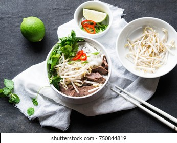 Traditional Vietnamese soup pho in a  white bowl with beef and rice noodles,  mint and cilantro, green onions, chili peppers, bean sprouts, and lime on a black background.  Asian food. Top view
