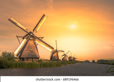Traditional village with dutch windmills and river at sunset, Holland, Netherlands.