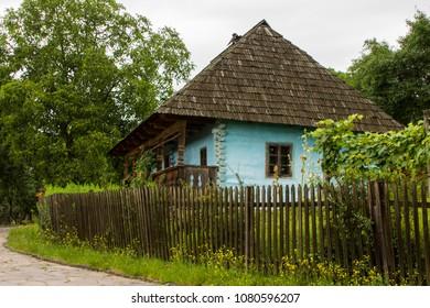 Traditional village historical building of Western Ukraine, where the roof is covered with wooden tiles. Skansen Uzhhorod. Ukraine