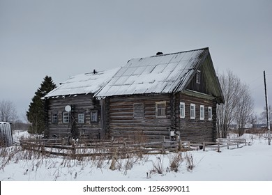 Traditional village house in winter in cloudy weather. Old northern residential architecture of Russia. Log cabin is called izba