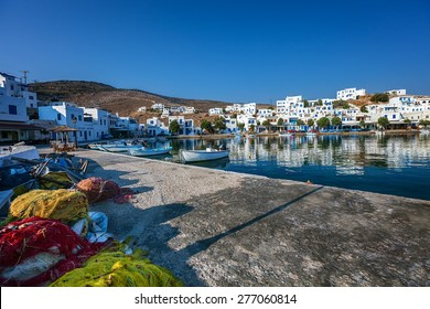 Traditional village of Panormos, in Tinos island, Greece, with fishing nets and fisher boats, on a calm morning
