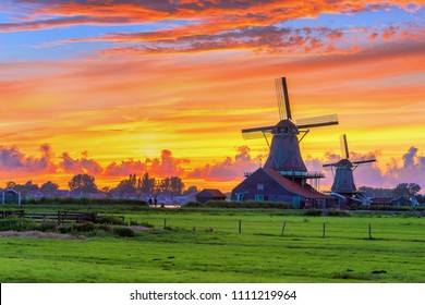 Traditional village at sunset, with dutch windmills, bridge and river on Zaanse Schans, Holland, Netherlands.