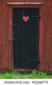 Traditional vintage restroom or lavatory outside with a heart sign on the black door. Sweden