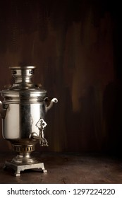 A traditional vintage water boiler pot for tea Russian Samovar. Close up view with copy space on dark brown wooden background