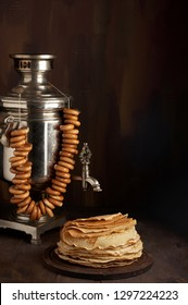 A traditional vintage water boiler pot for tea Russian Samovar with sushkie. Stack of thin pancakes blini. Close up view with copy space on dark brown wooden background