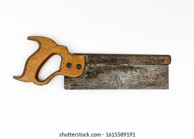Traditional vintage wooden handled short backsaw with a rusty metal blade shot from above in a white studio.