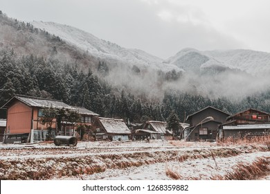 Traditional Wada House in Shirakawa-go, one of the world herritage site, during the winter with frozen rice field in the foreground and foggy mountain in the background