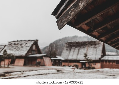 Traditional Wada House in Shirakawa-go, one of the world herritage site, during the winter with frozen rice field in the foreground. Focus on Water droplet from the roof.