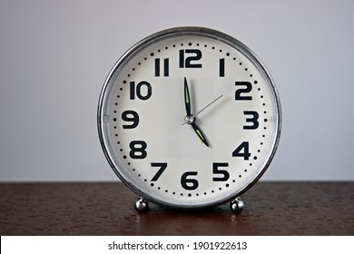 The traditional watch stands on dark furniture and shows 5:00 pm