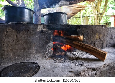 Traditional way of making food on open fire in old Indian kitchen in a village hotel, Kerala India. Ancient pots and pans on the stove over a natural fire using bio wood fuel for cooking in rural area