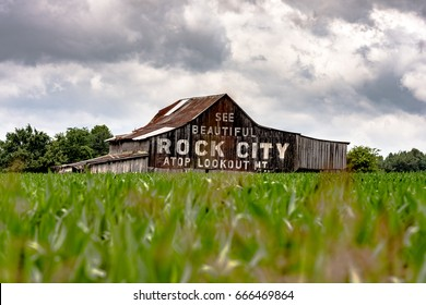 "Traditional weathered barn in southern Appalachia painted with ""See Rock City"" advertisement as viewed looking over a corn field"