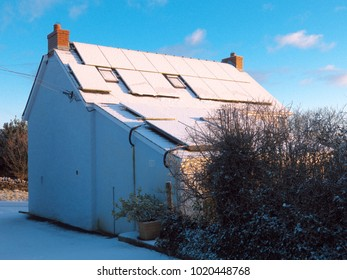 A traditional Welsh country cottage with snow on the photovoltaic and solar panels.