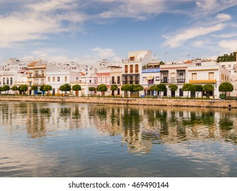 Traditional white architecture along the riverbank in Ayamonte, Huelva province, Andalucia, Spain.  The buildings and clouds are reflecting in the river that runs into the Guadiana River.