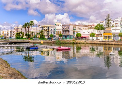 Traditional white architecture of the region along the riverbank in Ayamonte, Huelva province, Andalucia, Spain.  There are pleasure paddle boats on river that runs into the Guadiana River.