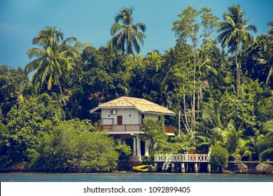 The traditional white building surrounded by the spectacular tropical forest next to the Madu Ganga, shallow water body. Balapitiya. South-western Sri Lanka.