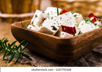 Traditional white cheese slices in oil with spices. Selective focus.