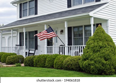 traditional white colonial home with American flag waving in the wind