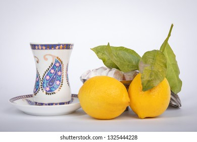 Traditional white color  armudu tea Cup with national patterns and buta print. Two lemons with a branch, Turkish delight,in an old copper sugar bowl.