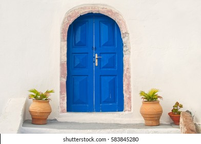 traditional white Greek house facade with blue door and flower pots, Santorini, Greece