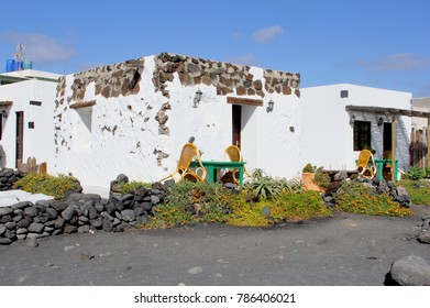 Traditional white houses in Canarian style with patio furniture at black volcanic beach, Lanzarote, Canary Islands, Spain