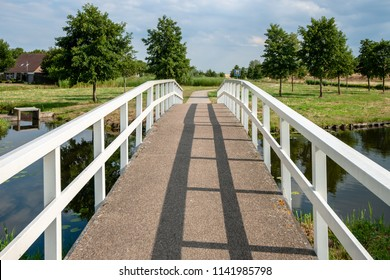 Traditional white wooden footbridge or cyclists bridge in a park or residential area. A Dutch landscape with bike path over water channels and walking areas