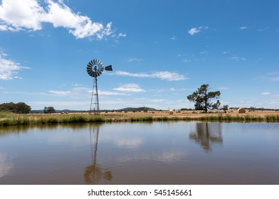 A traditional windmill beside the lake with golden hay bales in the field of Australian countryside.