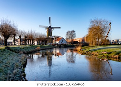 Traditional windmill and drawbridge at a stream with a thin layer of ice