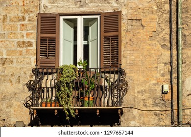 Traditional window and balcony with wooden shutters of old house in Palermo. Sicily, Italy