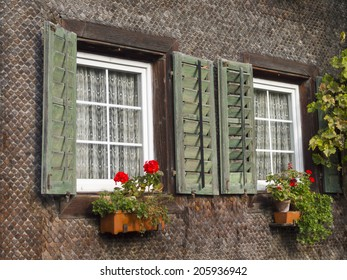 Traditional Window of Swiss wooden house with flower pot.