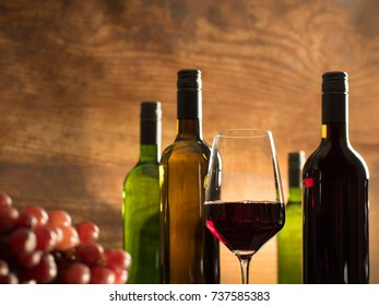 Traditional wine tasting atmosphere in a winery cellar with a glass of red wine in front of red grapes and wine bottles on a wooden background, closeup shot with blurry low depth of field