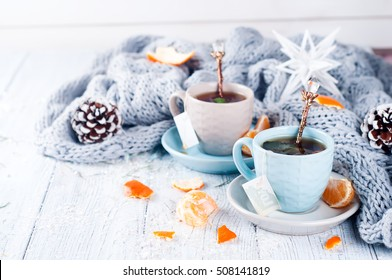 Traditional winter beverage tea with mint and tangerine. Christmas drink. Gray background with knitted scarf