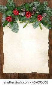 Traditional winter and christmas background border of flora of holly, ivy, mistletoe, snow covered leaf sprigs and pine cones on old parchment paper over oak wood.