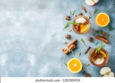 Traditional winter drinks, mulled wine cocktail with white wine, with spices, apple, orange. On a light blue table,