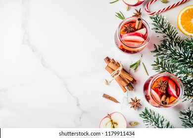 Traditional winter drinks, white and red mulled wine cocktail,  with white and red wine, spices, apple, orange. On white marble background copy space