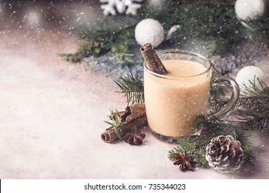 Traditional winter eggnog in glass mug with milk, rum and cinnamon, christmas decorations