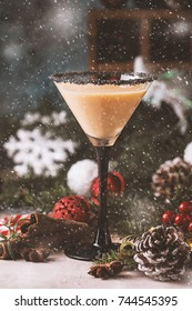 Traditional winter eggnog in martini glasses with milk, rum and cinnamon, christmas decorations
