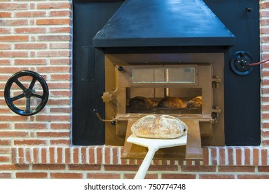 Traditional wood oven in a bakery and a baker shovel with a loaf