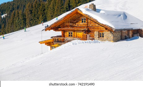 Traditional wooden alpine chalet on sunny winter day. Alps, Europe.