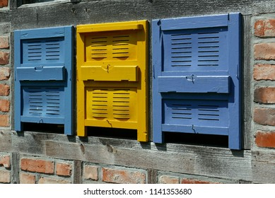 Traditional wooden bee boxes in blue and yellow
