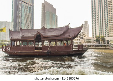 Traditional wooden boat with restaurant on the Chao Phraya river cruising tour. River view of the tourist boat takes visitors for sightseeing tour in Bangkok along the Chao Phraya River.