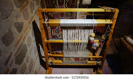 traditional wooden carpet weaving loom with colorful ropes