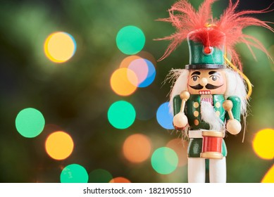 Traditional wooden Christmas nutcracker with a green background with colored lights out of focus, copy space