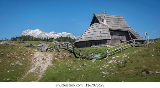Traditional wooden cottage on Velika planina (Big Pasture Plateau) in front of Kamnik-Savinja Alps, Slovenia